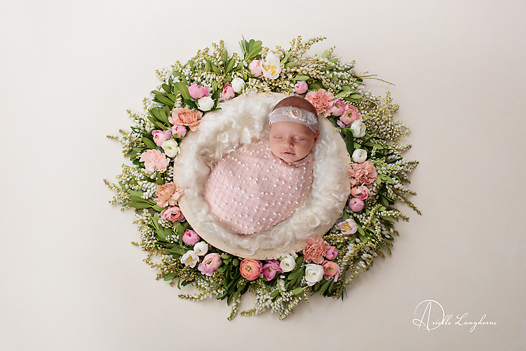 baby in nest of flowers